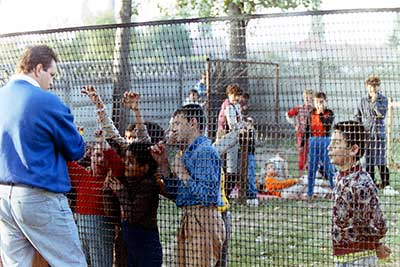 John talks to children through orphanage fence