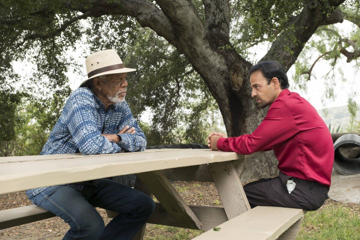 Morgan Freeman and Izidor at picnic table, talking