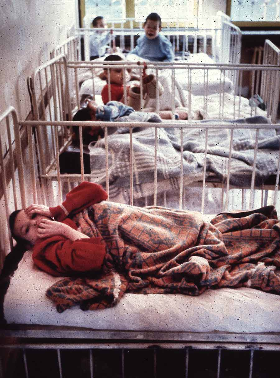 Children laying in orphanage cribs
