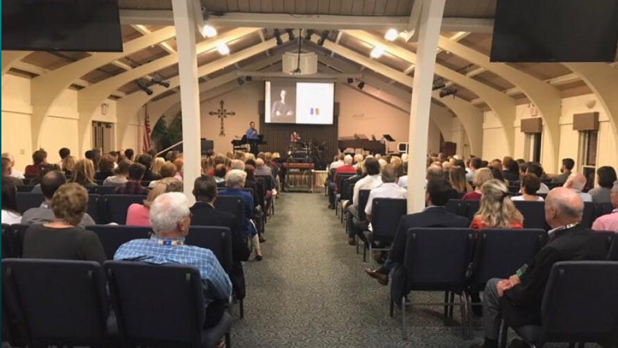 Izidor speaking at a church