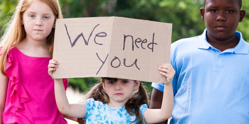 """3 children holding sign """"We need you"""""""